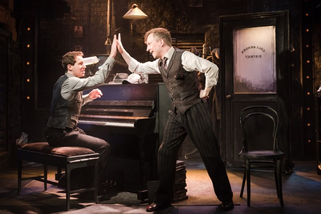 Two men high-fiving by a piano
